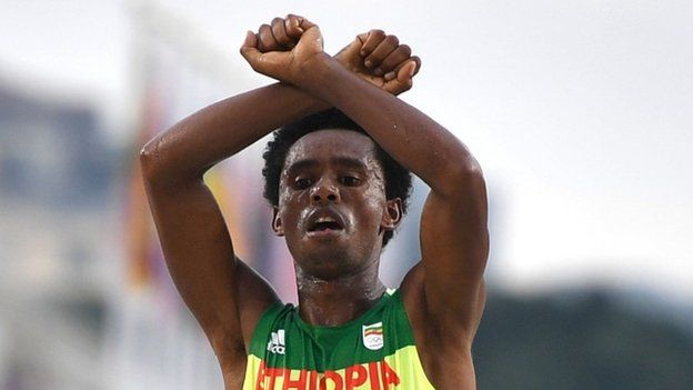 """Ethiopia's Feyisa Lilesa crossed his arms above his head at the finish line of the Men""""s Marathon athletics event of the Rio 2016 Olympic Games at the Sambodromo in Rio de Janeiro on August 21, 2016."""