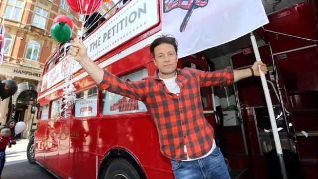 Jamie Oliver segurando balões, próximo a um ônibus