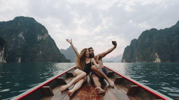 زوجان يهيمان بنفسيهما يلتقطان صورة سيلفي على قارب