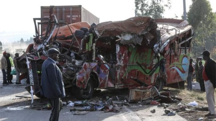 The bus, turned on the right side, is shown heavily damaged and crushed