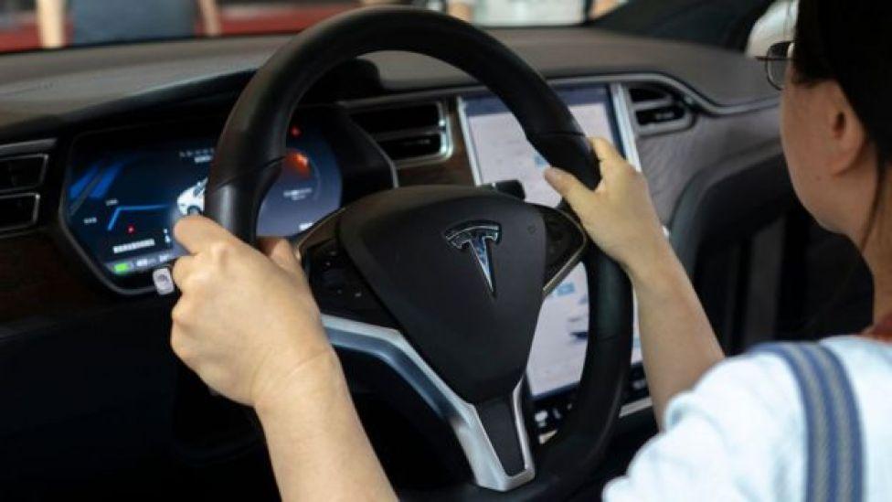 driver at wheel of Tesla
