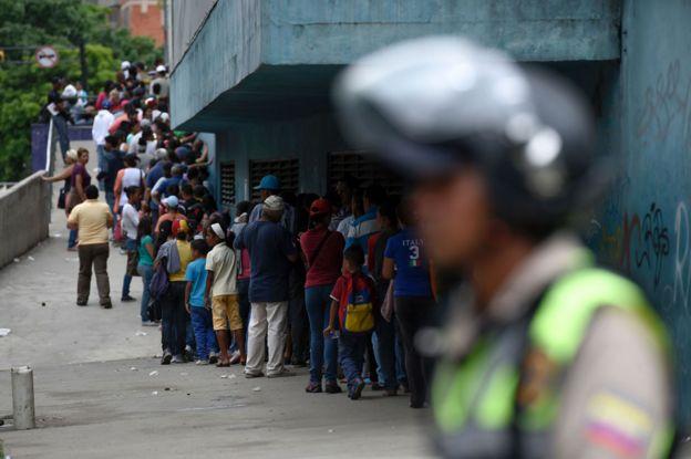 Polizei überwachen einen Supermarkt-Warteschlange in Petare, Caracas am 1. Juni 2016