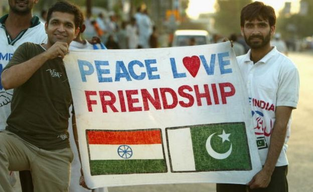 Cricket fans hold a sign which says 'Peace Love Friendship' after the first Pakistan v India one day international match played at the National Stadium March 13, 2004 in Karachi, Pakistan.