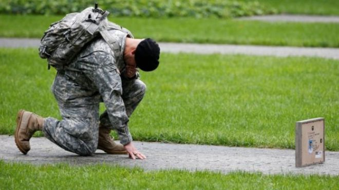 A soldier honours a victim at the memorial in New York City