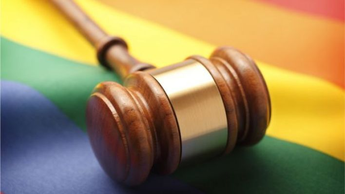 Martelo de madeira sobre bandeira do arco-íris