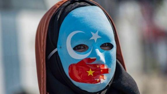 متظاهر ضد تصرفات الصين في شينجيانغ يرتدي قناعًا بألوان علم تركستان الشرقية قضية اليوغور