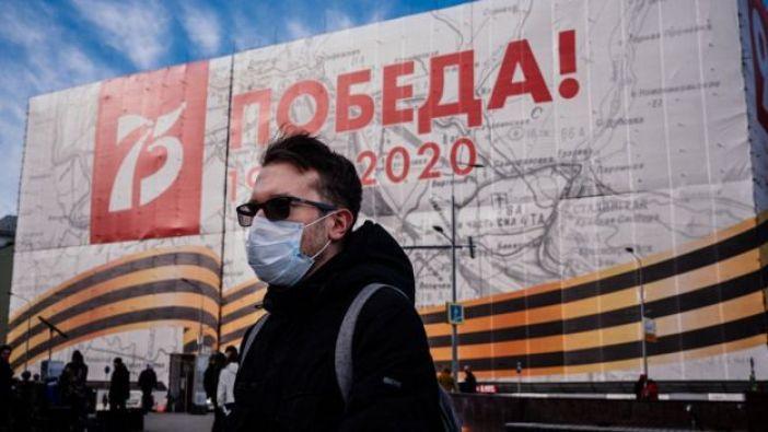 Un hombre con cubrebocas frente a un cartel del Día de la Victoria
