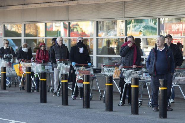 Clientes na fila do lado de fora de um supermercado.