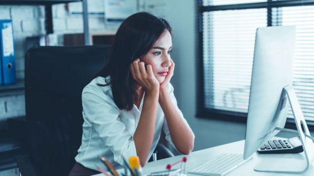 Mujer sentada frente a una computadora.