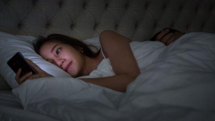 Mujer en la cama con el teléfono