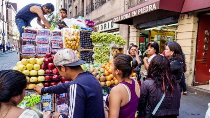 Un camión con frutas ofrece sus productos a los transeúntes.