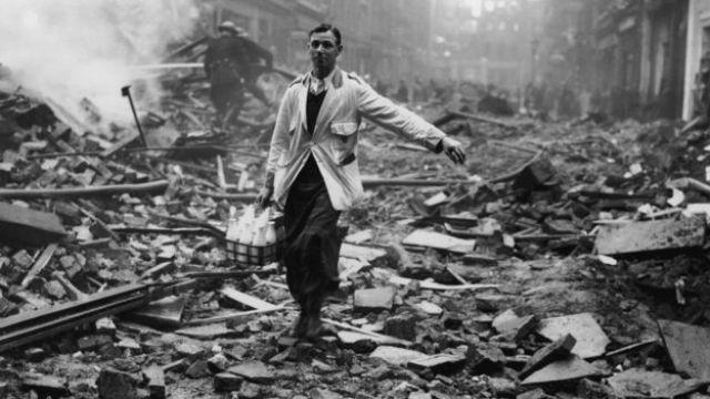 Homem carrega leite numa rua de Londres bombardeada na Segunda Grande Guerra
