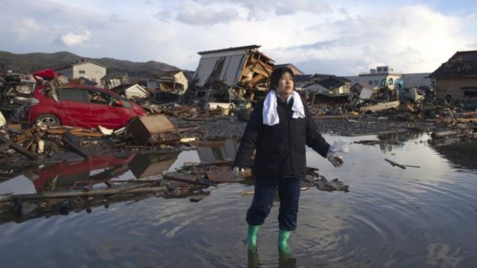 Una mujer de pie en el agua entre los destrozos causados por un tsunami