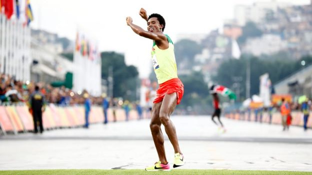Feyisa Lilesa of Ethiopia celebrates while crossing the finish line to take the second place in the men