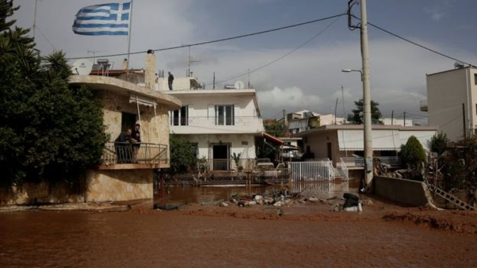 A Greek national flag flutters atop a terrace as locals observe a flooded street following a heavy rainfall in the town of Mandra