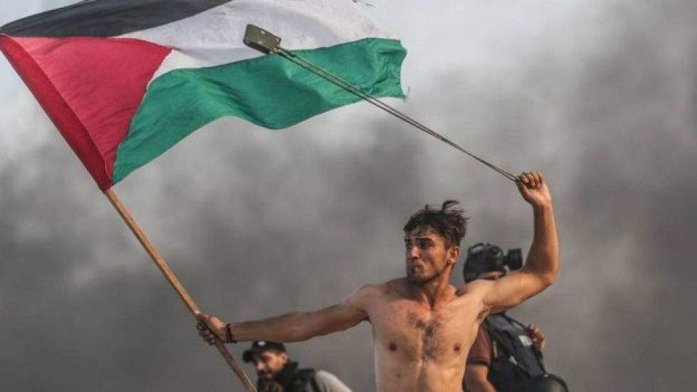 شاب يحمل العلم الفلسطيني بيد وفي الأخرى مقلاع يرمي به الجنود الإسرائيليين