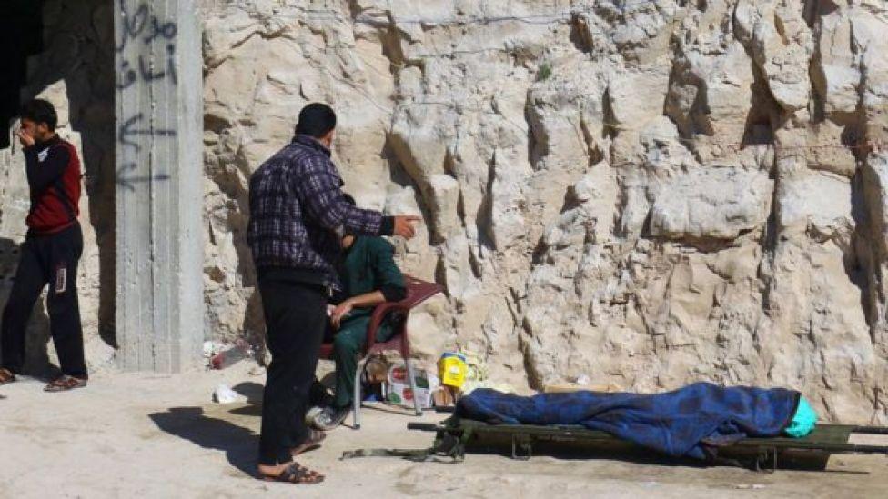 Homem próximo a maca com cadáver após ataque em Khan Sheikhoun no dia 4 de abril de 2017