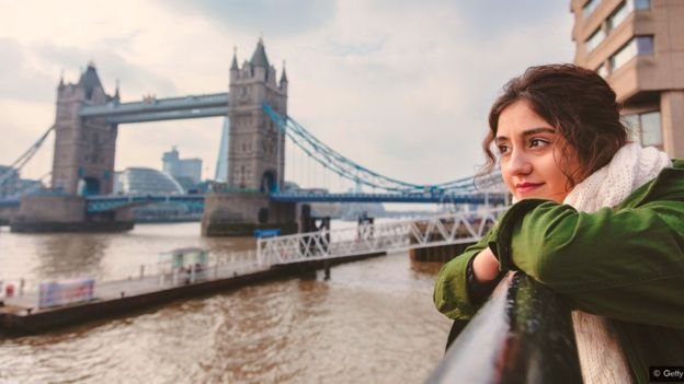 A woman contemplates the River Thames in London