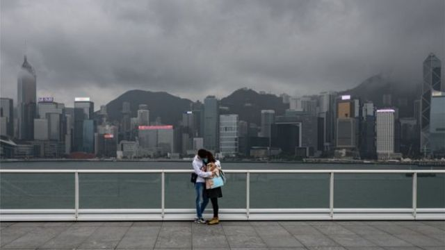 A couple stand on the observation desk at Tsim Sha Tsui in Hong Kong on February 14, 2020
