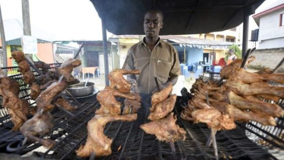 A man cooking chickens in Nigeria