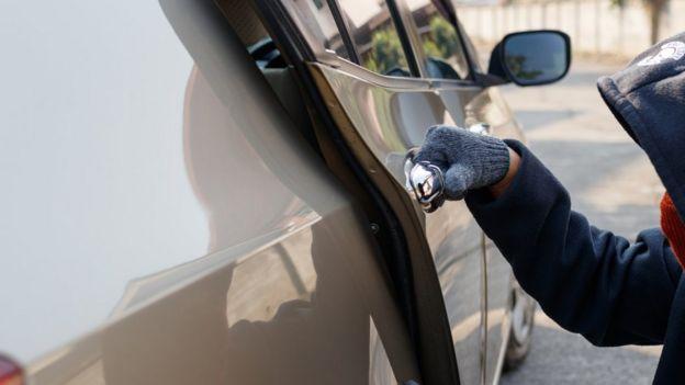 ladrón robando un auto