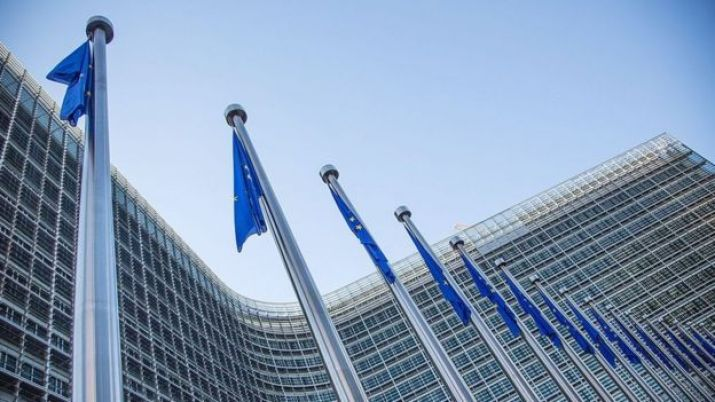 A view of European flags in front of the European Commission headquarters at the Berlaymont Building in Brussels