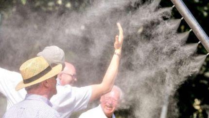 Pessoas se refrescam em equipamentos que disparam água