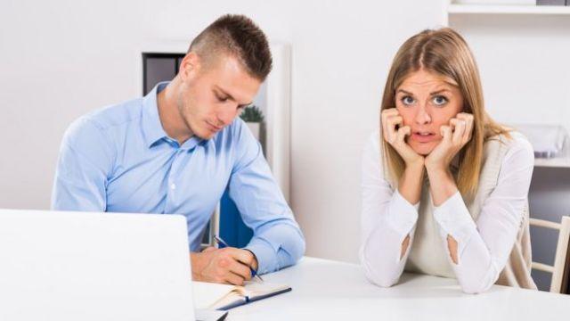 Una joven con cara de terror, junto a otro joven con una laptop