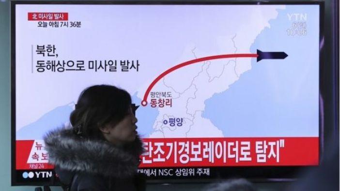 Una mujer camina delante de la pantalla de televisión mostrando un programa de noticias que informa sobre los lanzamientos de misiles de Corea del Norte, en la estación de tren de Seúl en Seúl, Corea del Sur.
