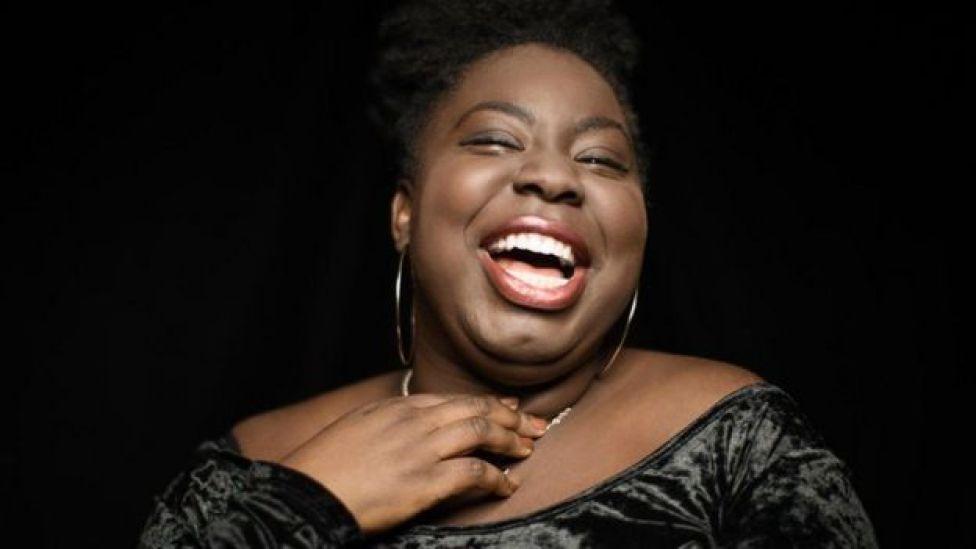 Mujer de raza negra y corpulenta sonriendo.