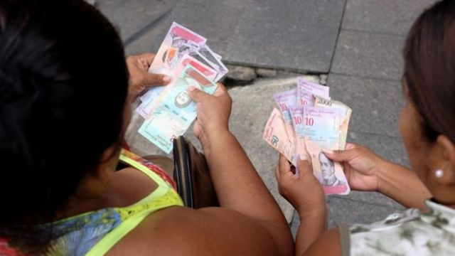 Mujeres con los nuevos billetes de Venezuela