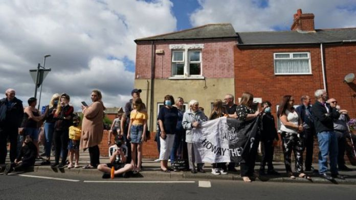Well-wishers line the street in Ashington with some holding a Newcastle United flag
