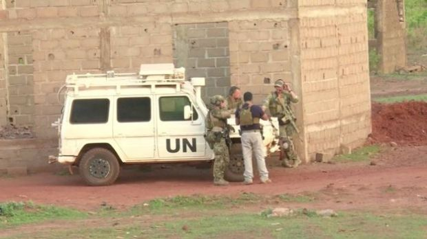 French soldiers stand around a United Nations vehicle following an attack where gunmen stormed Le Campement Kangaba in Dougourakoro
