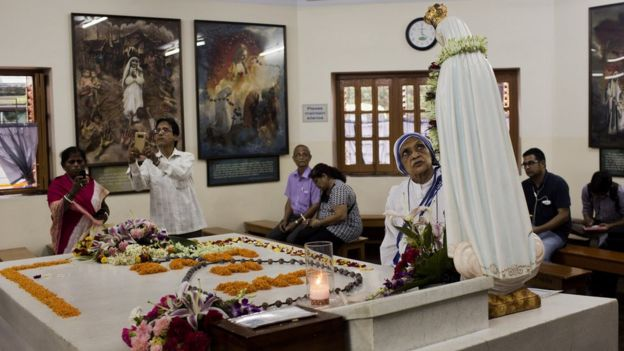 People gather around the tomb of Mother Teresa inside the Mother house in Kolkata, India, Saturday, September 3