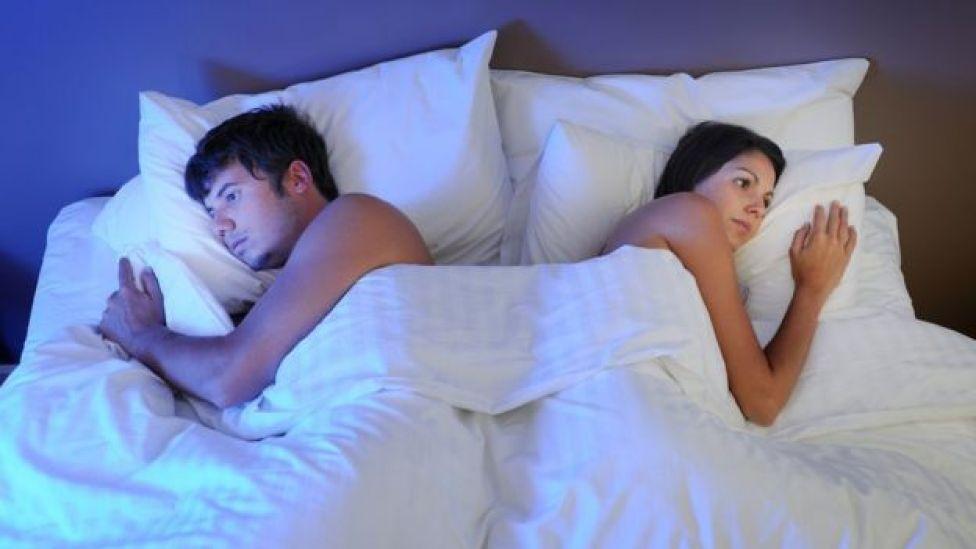Un pareja formaa por un hombre y una mujer en la cama, volteados el uno del otro.