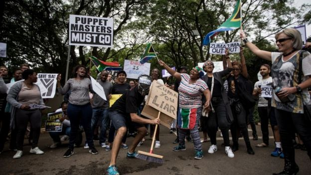 """Demonstrators holding signs such as """"Puppet masters must go"""" """"Zuma you liar"""""""