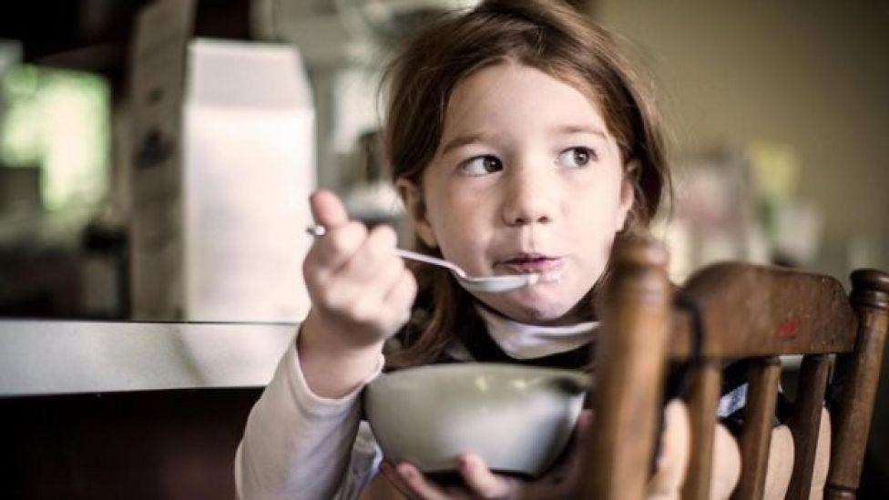 Una niña comiendo de un plato de cereal