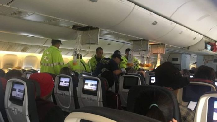 Emergency workers assist passengers of Air Canada AC 33 flight, which diverted to Hawaii after turbulence