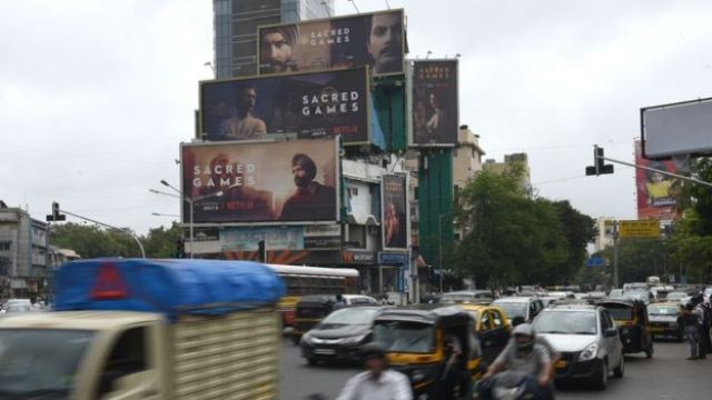 This photo taken on July 4, 2018 shows Indian commuters travelling past large billboards for 'Sacred Games', the upcoming Indian series on Netflix, in Mumbai.
