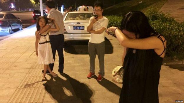 People stand in the street in Binhai, in the Tianjin area 12/08/2015