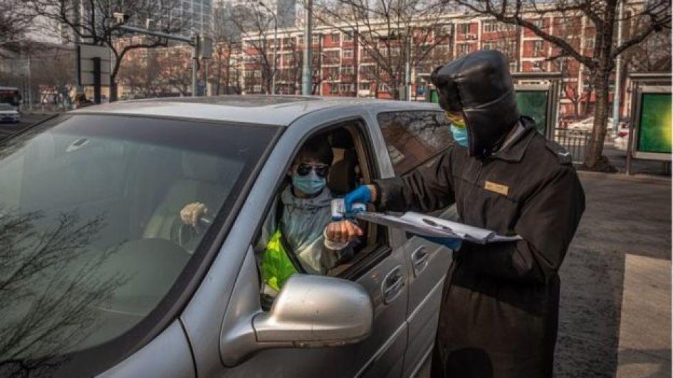 Guardia de seguridad toma la temperatura de un pasajero en un vehículo en China, 11 de febrero de 2020.