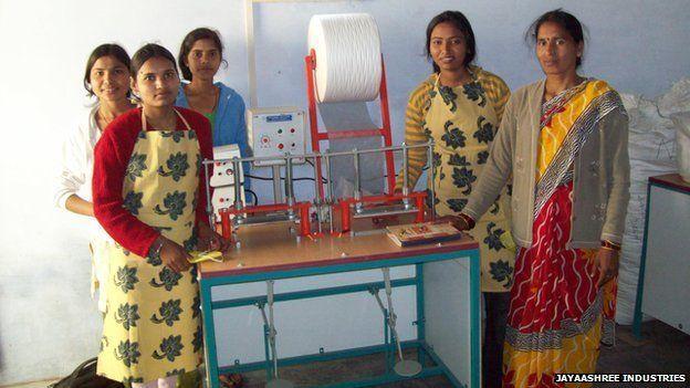 Indian school girls stand before the sanitary pad machine