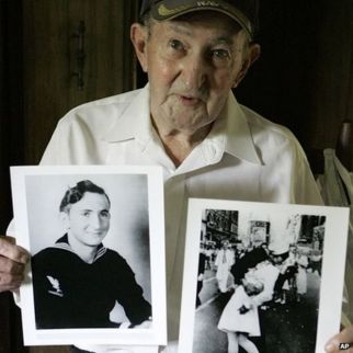 Glenn McDuffie holds a portrait of himself as a young man, left, and a copy of Alfred Eisenstaedt's iconic Life magazine shot of a sailor (31 July 2007)