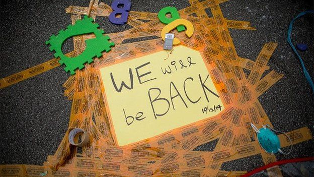 'We Will Be Back' is displayed on a sign taped to the road outside Hong Kong's Government complex on December 11, 2014 in Hong Kong