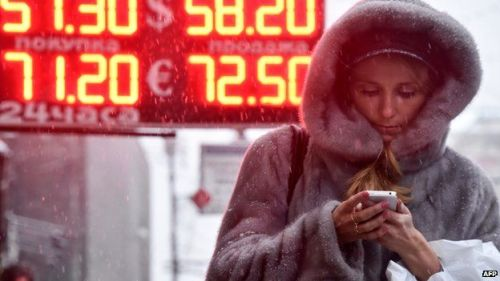 A woman walks past a board listing foreign currency rates against the Russian rouble outside in central Moscow on December 12, 2014.