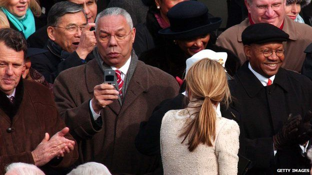 Outgoing Secretary of State Colin Powell takes a picture with his phone of President George W Bush as he leaves the platform at the end of the swearing-in ceremony 20 January 2005