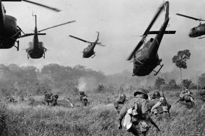Hovering US Army helicopters pour machine-gun fire into the tree line to cover the advance of South Vietnamese ground troops as they attack a Viet Cong north of Tay Ninh, near the Cambodian border, March 1965