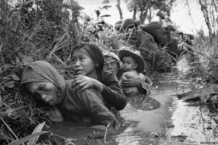 Women and children take cover from heavy fire about near Saigon, Vietnam 1 January 1966