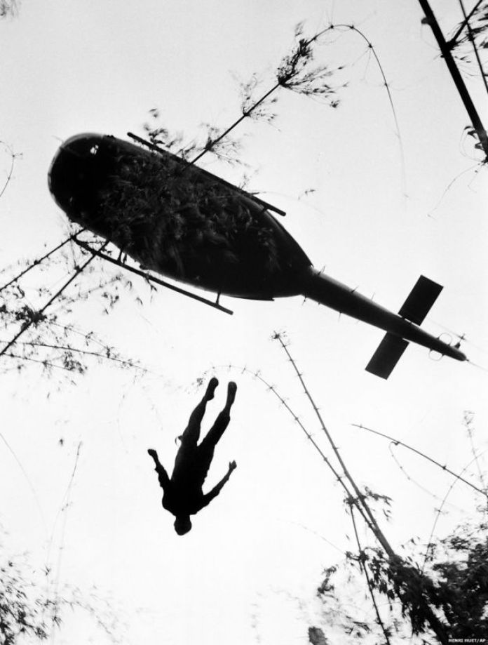 The body of an American paratrooper killed in action in the jungle near the Cambodian border is raised up to an evacuation helicopter in War Zone C, Vietnam, 14 May 1966