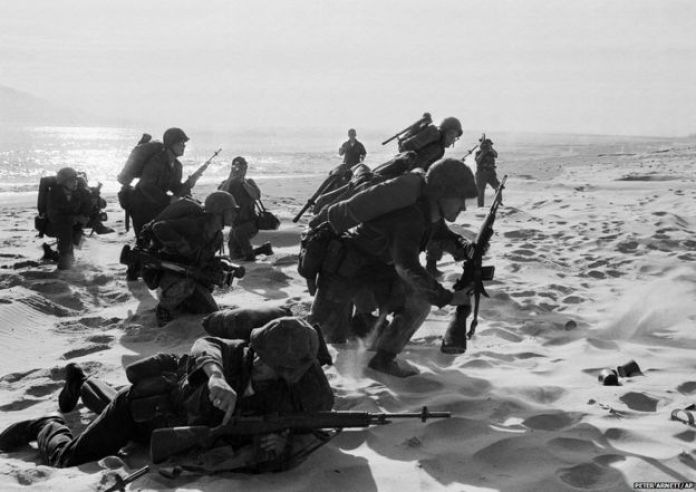 Freshly landed US Marines make their way through the sands of Red Beach at Da Nang, 10 April 1965. They were on their way to reinforce the air base as South Vietnamese Rangers battled guerrillas about three miles south of the beach.